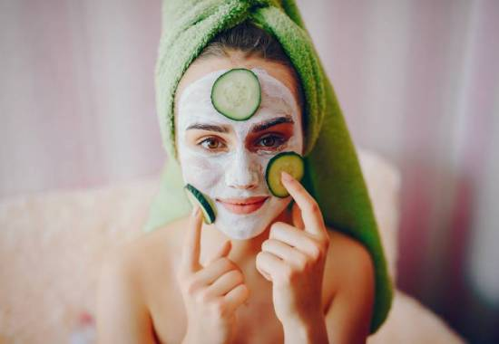 Beautiful girl sitting on the couch in the room. Lady in a green towel and with cucumber on her face